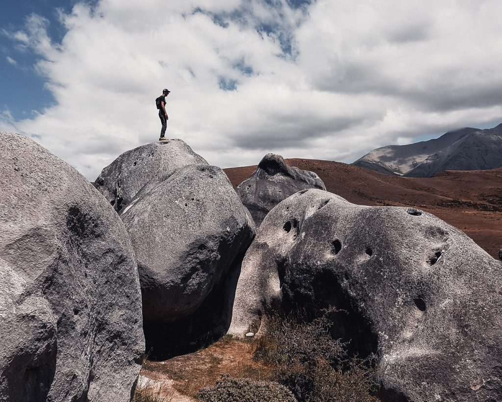 Algirdas standing on top of an egg-shaped boulder at Castle Hill, New Zealand