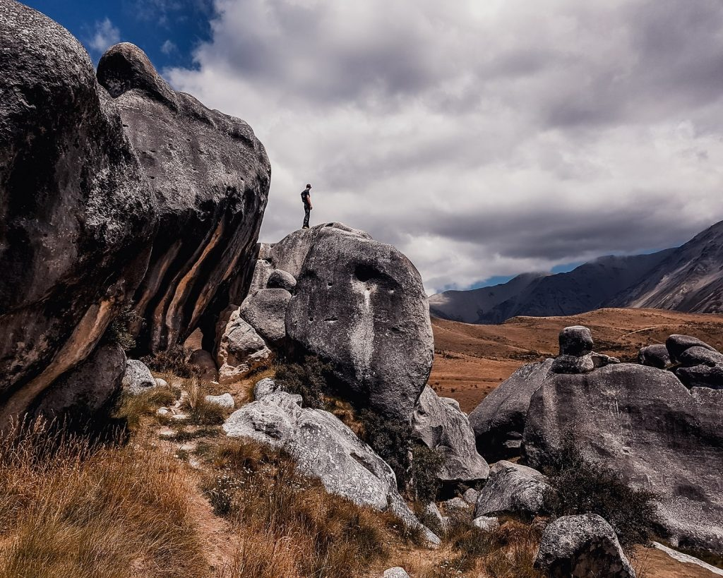 Guy standing on gigantic boulders at Kura Tawhiti conservation area, New Zealand