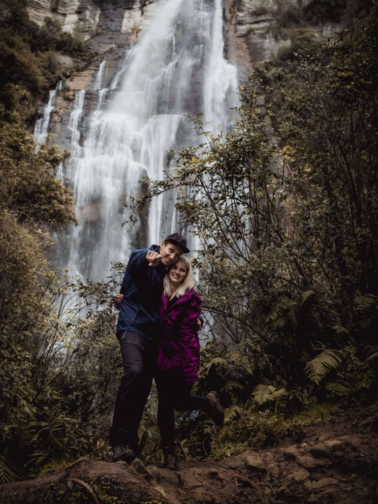 Traveling couple in front of Shine falls, New Zealand